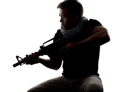 militant: Silhouette of a model posing as a military soldier with a rifle and shemagh scarf