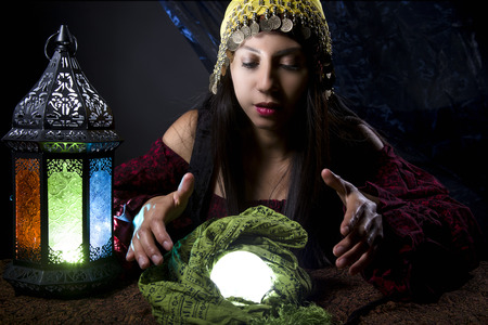 soothsayer: Woman dressed in a Halloween costume looking into a crystal ball Foto de archivo