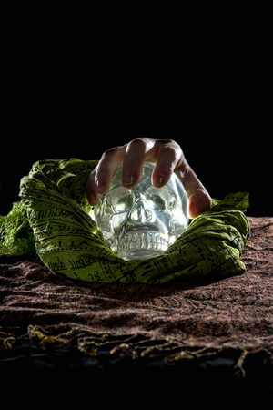 death head holding: Creepy hand grabbing a crystal skull in a dark background Stock Photo