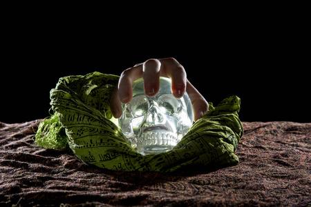 Creepy hand grabbing a crystal skull in a dark background Stock Photo