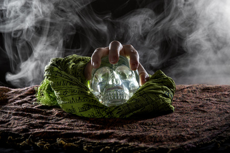 grabbing: Spooky smoky scene of a hand grabbing a crystal skull