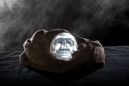 satanist: Creepy crystal skull with smoke in a dark scary setting