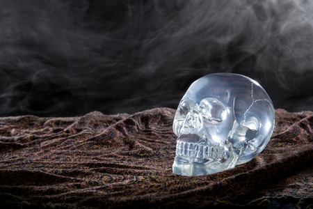 smoky black: Creepy crystal skull with smoke in a dark scary setting
