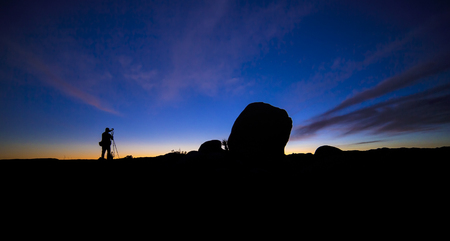 morning blue hour: Silhouette of a photographer working and hiking in a desert landscape at night
