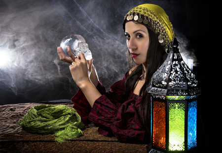 Female psychic or fortune teller holding a crystal skull trying to communicate with the dead Stock Photo