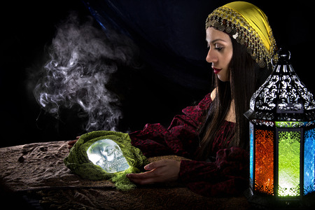 esoterism: Female psychic or fortune teller holding a crystal skull trying to communicate with the dead Stock Photo
