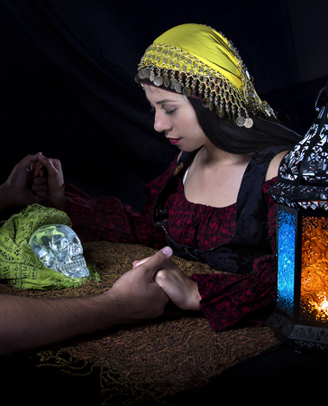 diviner: Psychic or fortune teller gypsy with a client doing a seance telepathic ritual