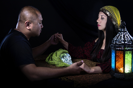 psiquico: Psychic or fortune teller gypsy with a client doing a seance telepathic ritual