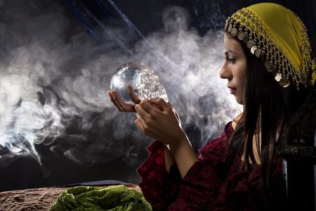soothsayer: Mujer cajero psíquica o la fortuna que sostiene una calavera de cristal tratando de comunicarse con los muertos Foto de archivo