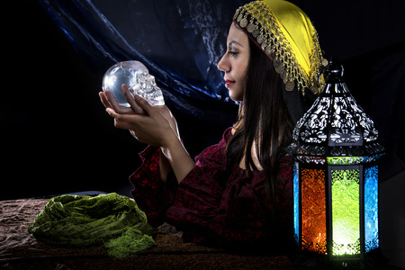 palmist: Female psychic or fortune teller holding a crystal skull trying to communicate with the dead Stock Photo