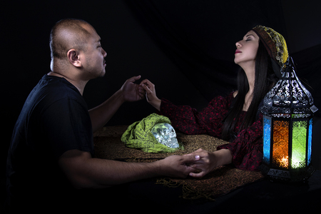 seance: Psychic or fortune teller gypsy with a client doing a seance telepathic ritual