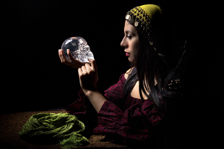 diviner: Female psychic or fortune teller holding a crystal skull trying to communicate with the dead Stock Photo