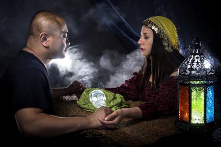 psychic: gitano cajero psíquica o la fortuna con un cliente haciendo un ritual telepática sesión Foto de archivo
