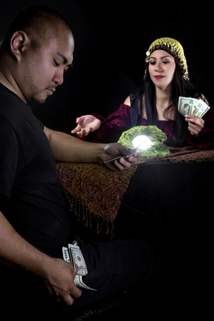 astrologist: Female fortune teller or con artist swindling money from a male customer via fraud Stock Photo