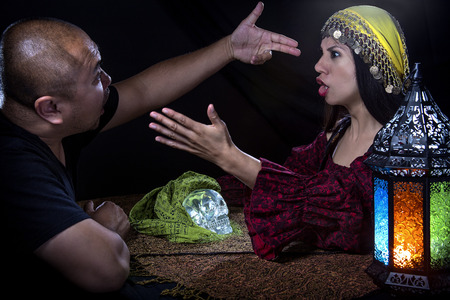Skeptical man arguing with a female con artist fortune teller or spirit medium about fraud