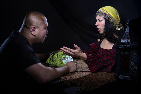 skepticism: Skeptical man arguing with a female con artist fortune teller or spirit medium about fraud