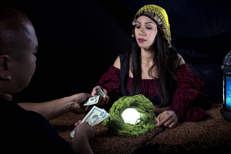 Female fortune teller or con artist swindling money from a male customer via fraud Stock Photo