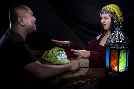 seance: Skeptical man arguing with a female con artist fortune teller or spirit medium about fraud