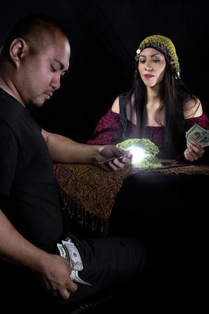 swindler: Female fortune teller or con artist swindling money from a male customer via fraud Stock Photo