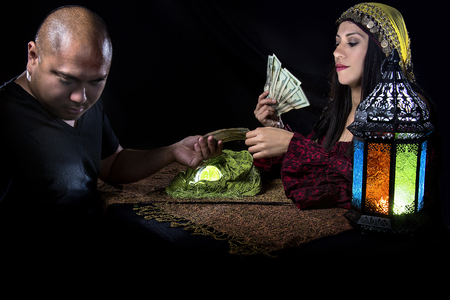 Female fortune teller or con artist swindling money from a male customer via fraud Stock Photo