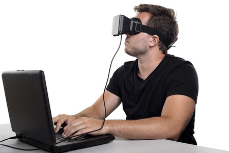 Virtual Reality gamer wearing headset tethered to a gaming pc Stock Photo