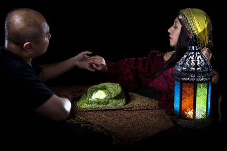 Gullible male client is giving a fraudulent psychic a diamond ring Stock Photo