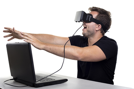 computer simulation: Virtual Reality gamer wearing headset tethered to a gaming pc Stock Photo