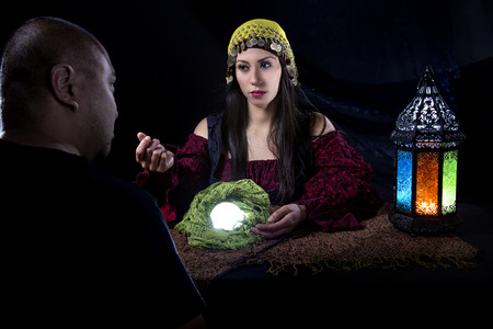 Gullible patron with scam artist or fraudulent psychic fortune teller