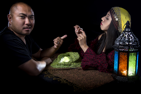 naivete: Gullible male client is giving a fraudulent psychic a diamond ring Stock Photo