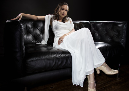ambiguous: Bridal modeling modern fashion trend of simple but elegant thin wedding dress in retro or art deco style.  Bride on couch with shoulder scarf and bridal gown.
