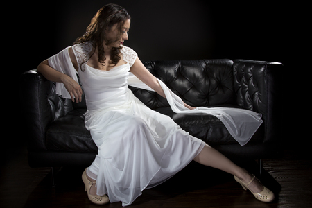 modelos posando: Bridal modeling modern fashion trend of simple but elegant thin wedding dress in retro or art deco style.  Bride on couch with shoulder scarf and bridal gown.