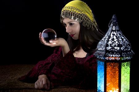 Psíquica o contador del tiempo mirando a una bola de cristal para predecir el destino o futuro. Astrología. Adivino. Foto de archivo - 65441134