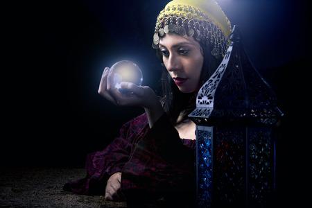 soothsayer: Psíquica o contador del tiempo mirando a una bola de cristal para predecir el destino o futuro. Astrología. Adivino.