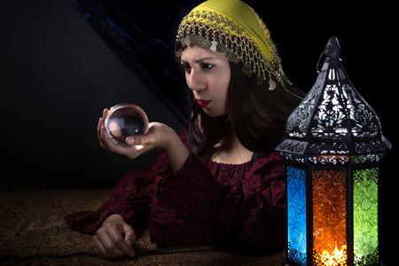 psychic: Psíquica o contador del tiempo mirando a una bola de cristal para predecir el destino o futuro. Astrología. Adivino.