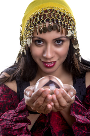 psychic: Close up of female fortune teller or psychic with clear crystal ball for composites.  Facial expressions indicate she is seeing a vision on in the orb. Stock Photo