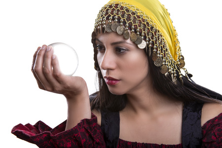 Close up of female fortune teller or psychic with clear crystal ball for composites.  Facial expressions indicate she is seeing a vision on in the orb. Stock Photo