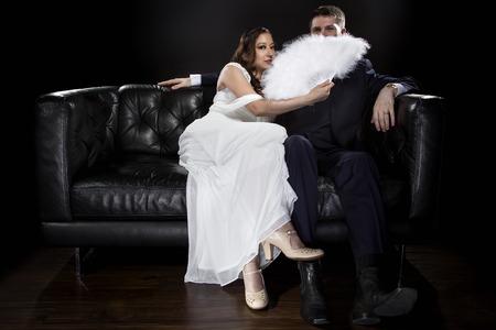 Brautpaar in einer Beziehung hinter einem Ventilator küssen oder flüsternd versteckt und Retro-noir-Stil Anzug und Kleid trägt. Datenschutzkonzept. Standard-Bild - 70002355