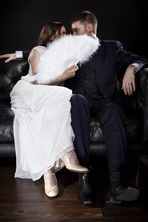 Brautpaar in einer Beziehung hinter einem Ventilator küssen oder flüsternd versteckt und Retro-noir-Stil Anzug und Kleid trägt. Datenschutzkonzept. Standard-Bild - 70002354