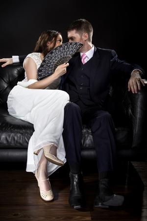 Brautpaar in einer Beziehung hinter einem Ventilator küssen oder flüsternd versteckt und Retro-noir-Stil Anzug und Kleid trägt. Datenschutzkonzept. Standard-Bild - 70002358