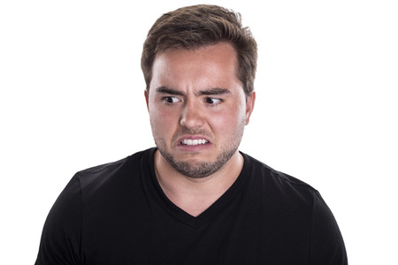 desprecio: Cerca de la cara masculina joven que mira disgustado sobre un fondo blanco