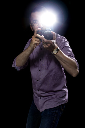 paparazzi periodista o fotógrafo de sexo masculino editorial utilizando un flash estroboscópico del speedlight en la oscuridad Foto de archivo