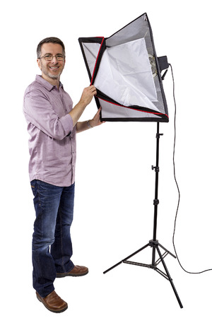 Male photographer showing or demonstrating how to use a soft box studio light for photography on a white background.
