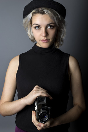 filmmaker: Woman holding a vintage video camera posing as a director, filmmaker, or cinematographer in the movie industry.  The image depicts creative arts.