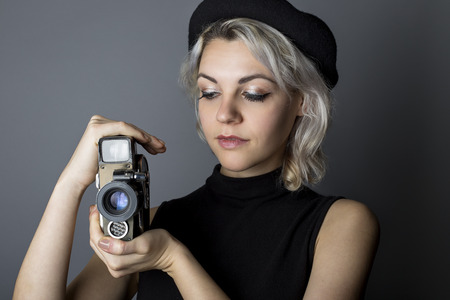 Woman holding a vintage video camera posing as a director, filmmaker, or cinematographer in the movie industry.  The image depicts creative arts.