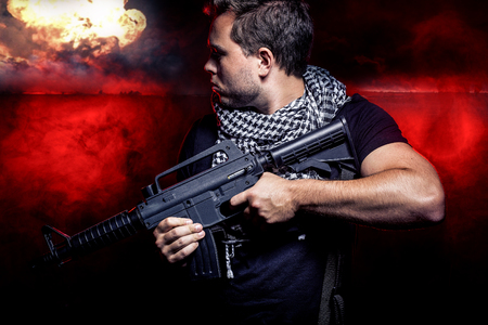 Soldier with a gun surviving bombs that are weapons of mass destruction or a nuclear war. The image depicts warfare and apocalyptic WW3. Stock Photo