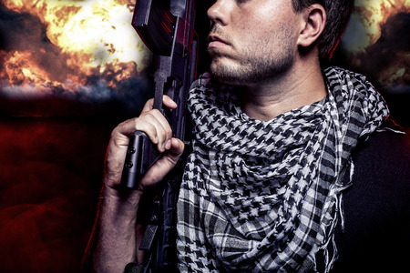 surviving: Soldier with a gun surviving bombs that are weapons of mass destruction or a nuclear war. The image depicts warfare and apocalyptic WW3. Stock Photo