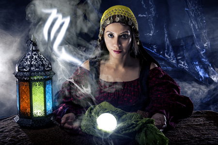psychic: Psychic or fortune teller with crystal ball and horoscope zodiac sign of Scorpio Stock Photo
