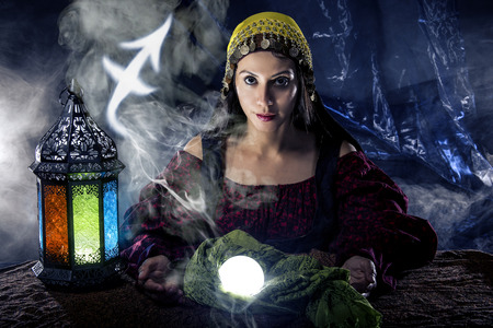 astrologist: Psychic or fortune teller with crystal ball and horoscope zodiac sign of Sagitarius Stock Photo