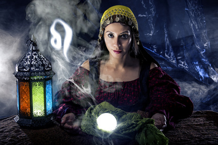 astrologist: Psychic or fortune teller with crystal ball and horoscope zodiac sign of Leo Stock Photo