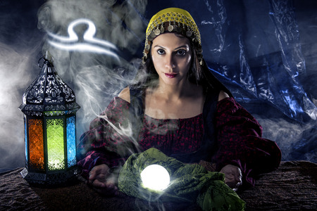 astrologist: Psychic or fortune teller with crystal ball and horoscope zodiac sign of Libra